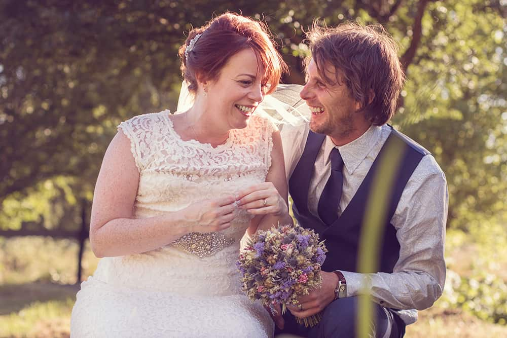 a bride and groom laughing in the sun