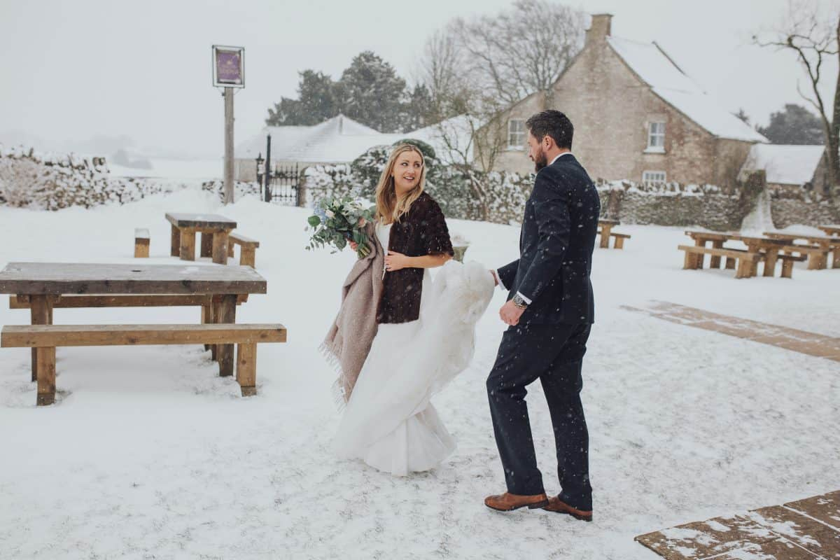 Bride and Groom walk outside in the snow at their Cotswolds wedding at the Old Lodge Minchinhampton