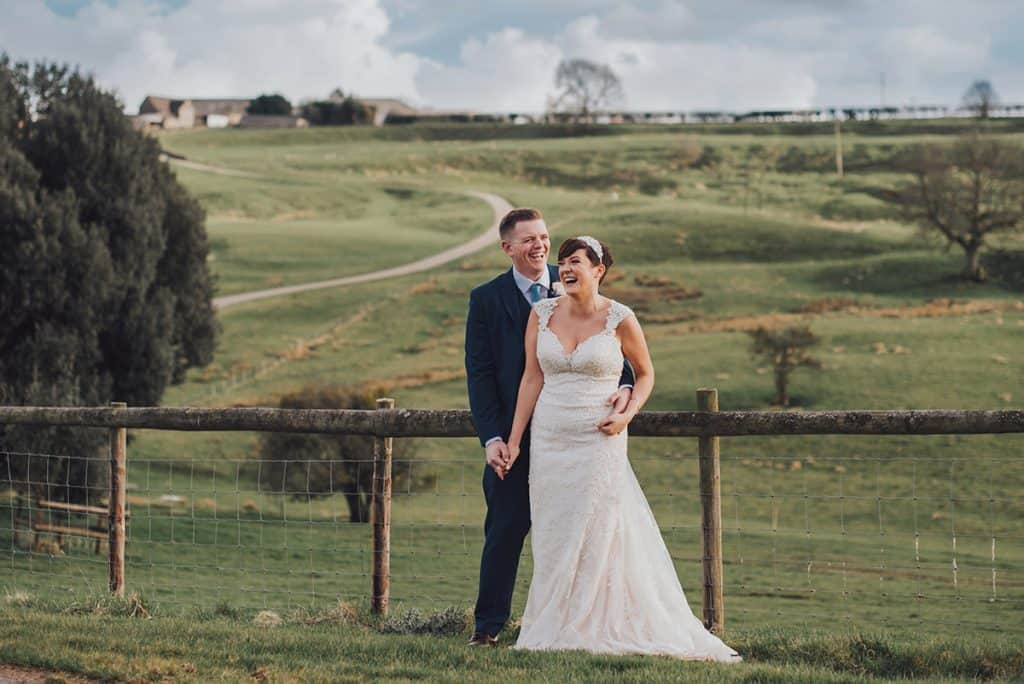 Bride and Groom laugh in front of rolling hills on their wedding day at Kingscote Barn