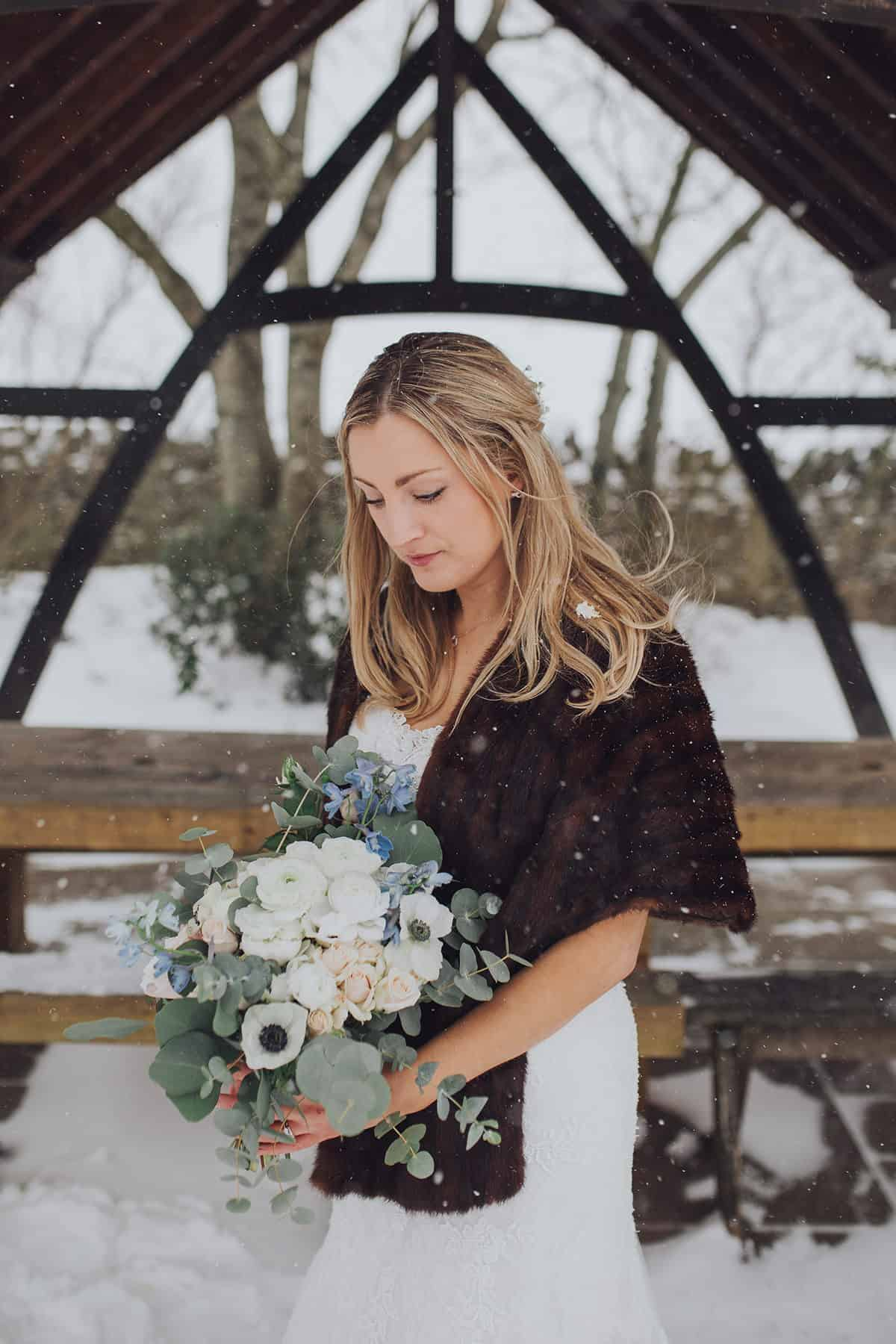 Bride looking at bouquet whilst standing outside in the snow
