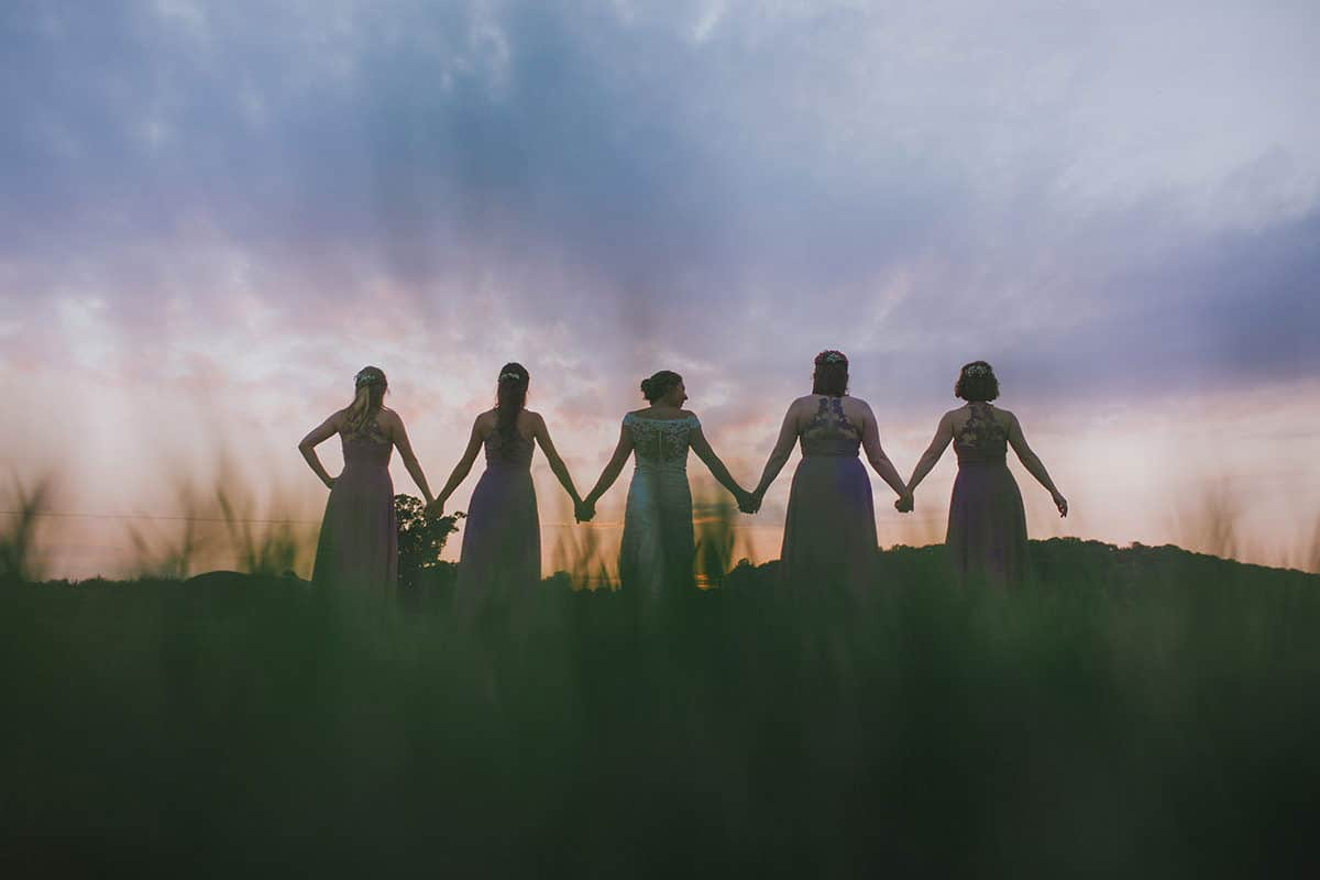 bridesmaids and bride holding hands facing away at sunset