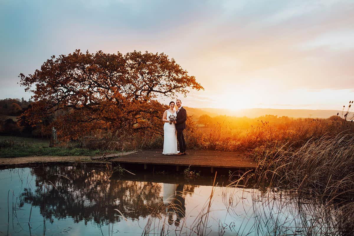 folly farm wedding couple by a pond at sunset
