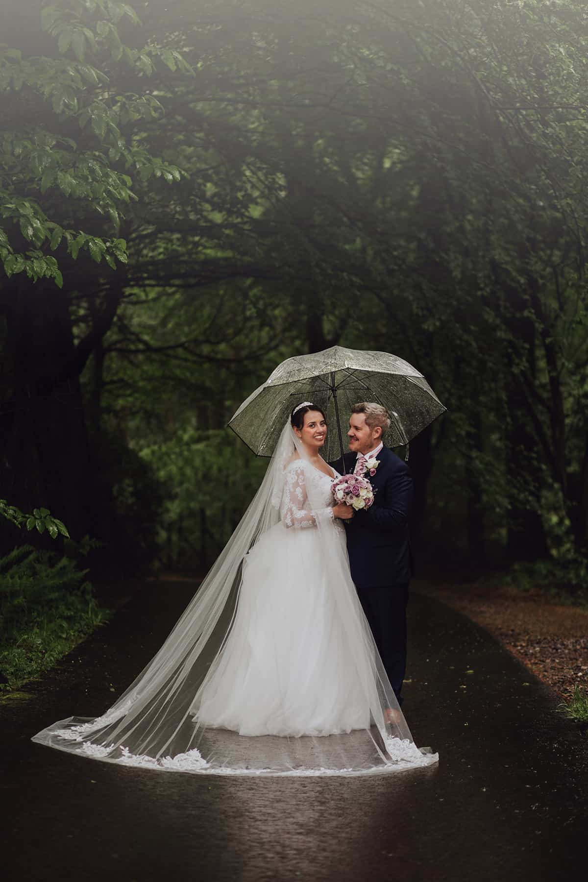 Bride and groom with cathedral length veil in the rain under umbrella