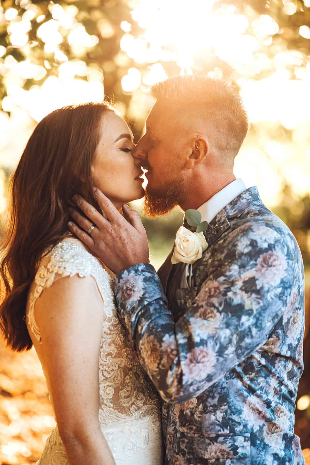 bride and groom in floral suit kissing at sunset