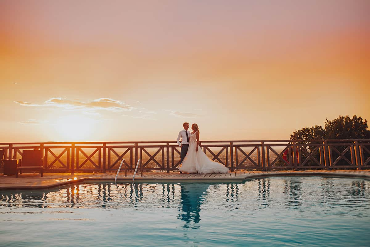 bride and groom in tuscany by swimming pool at sunset