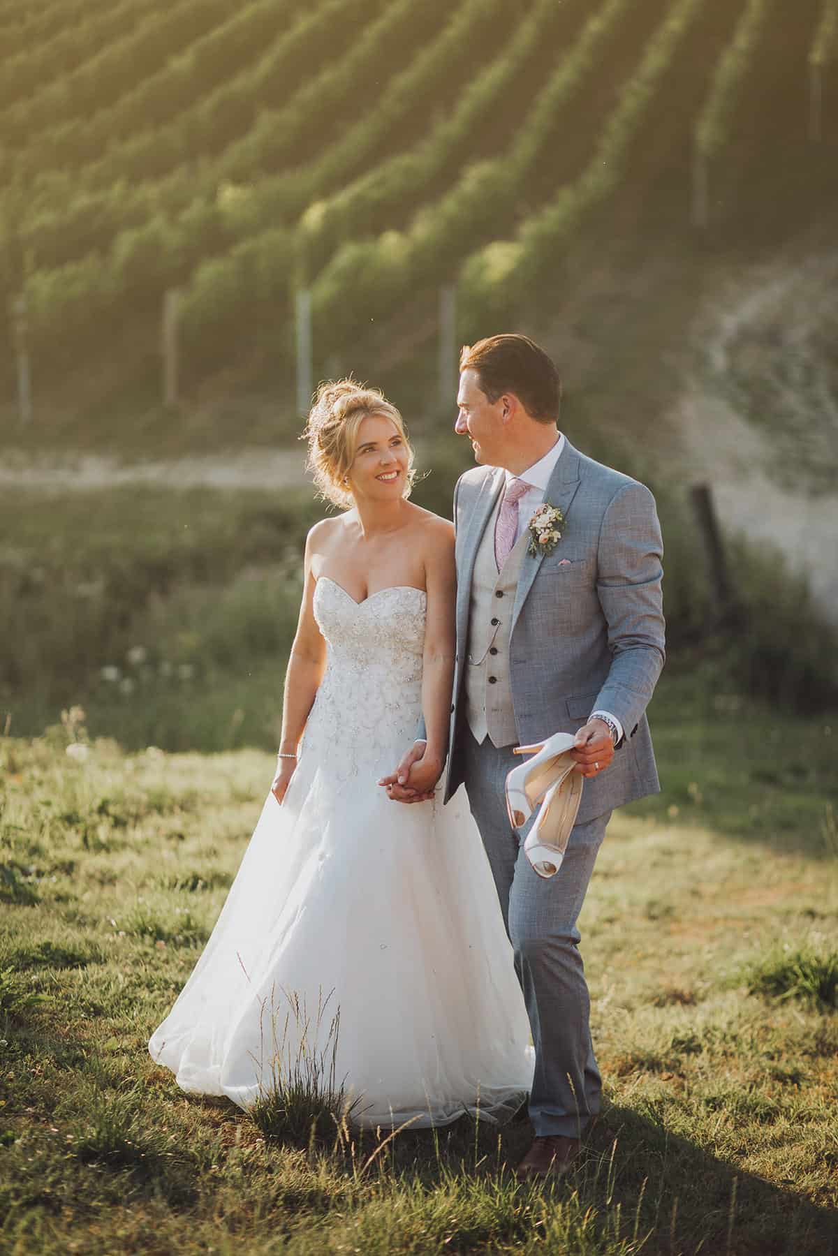 bride looks at groom as they walk through vineyards, he holds her shoes