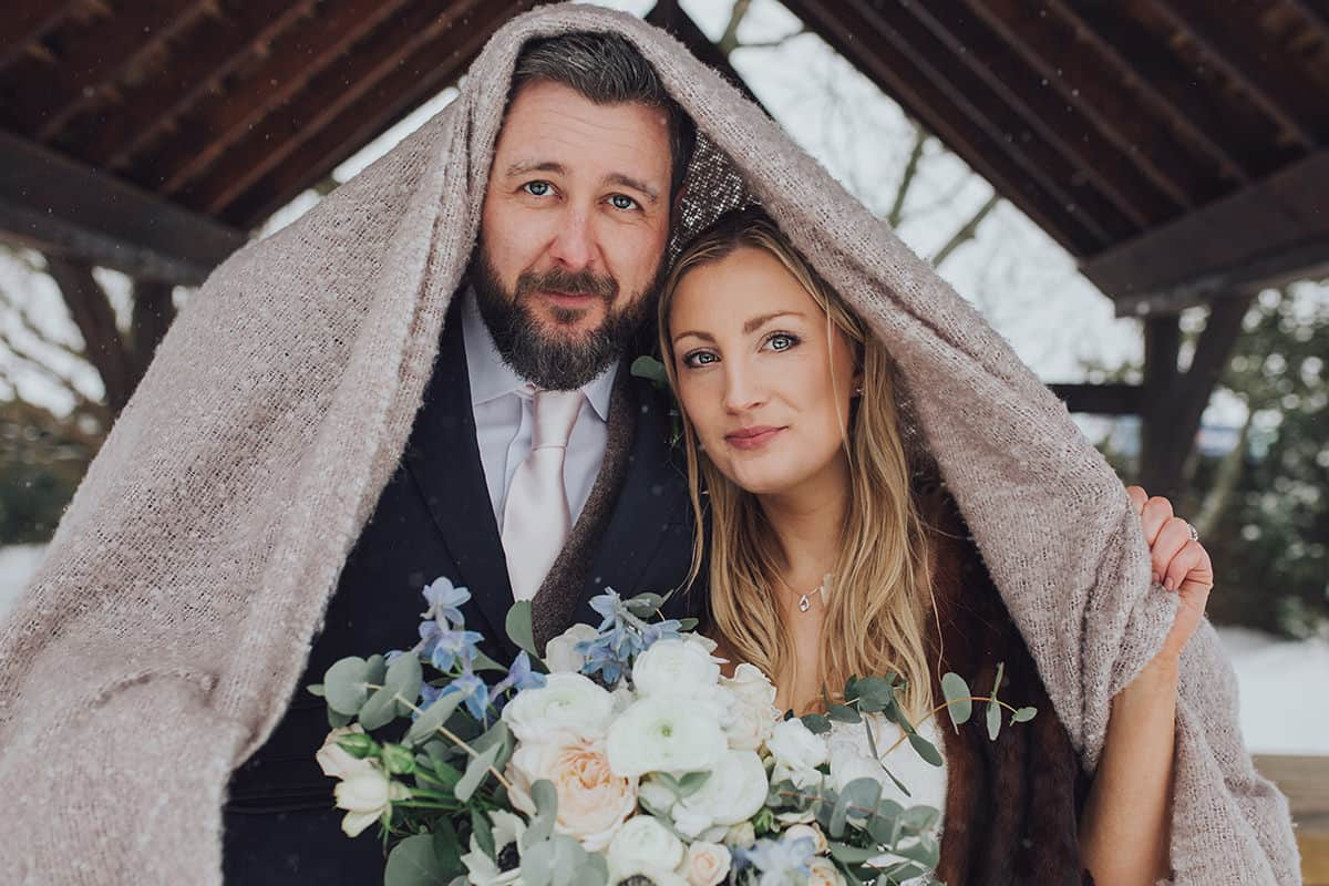 bride and groom under a blanket on their wedding day sheltering from the snow