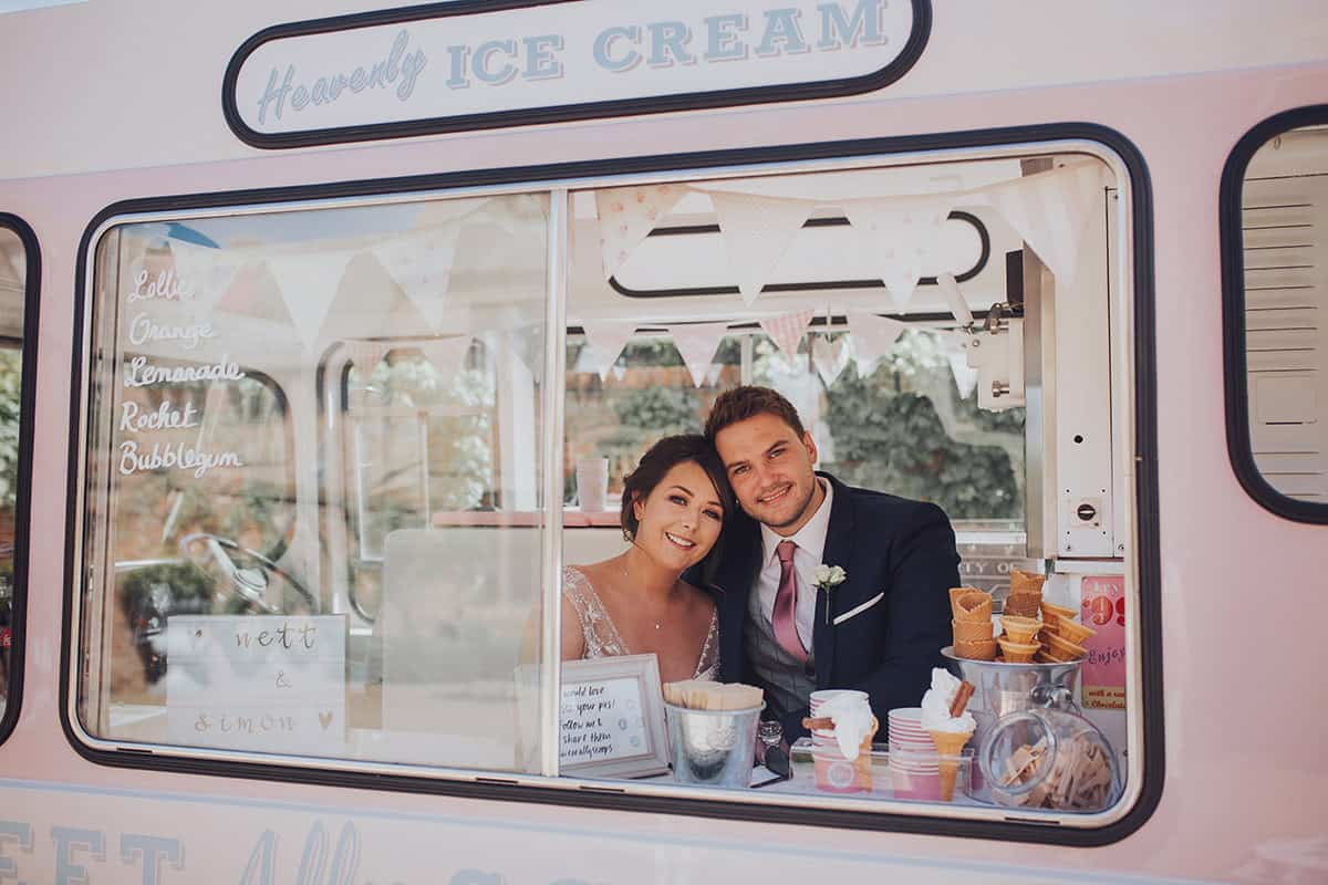 Bride and Groom sitting in pink ice cream truck smiling