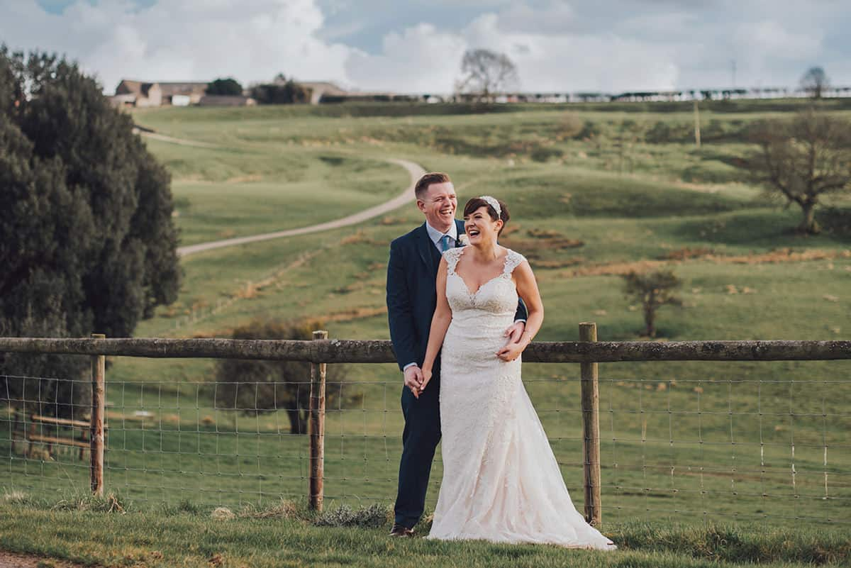 Bride and groom laughing together in front of hills at Kingscote Barn