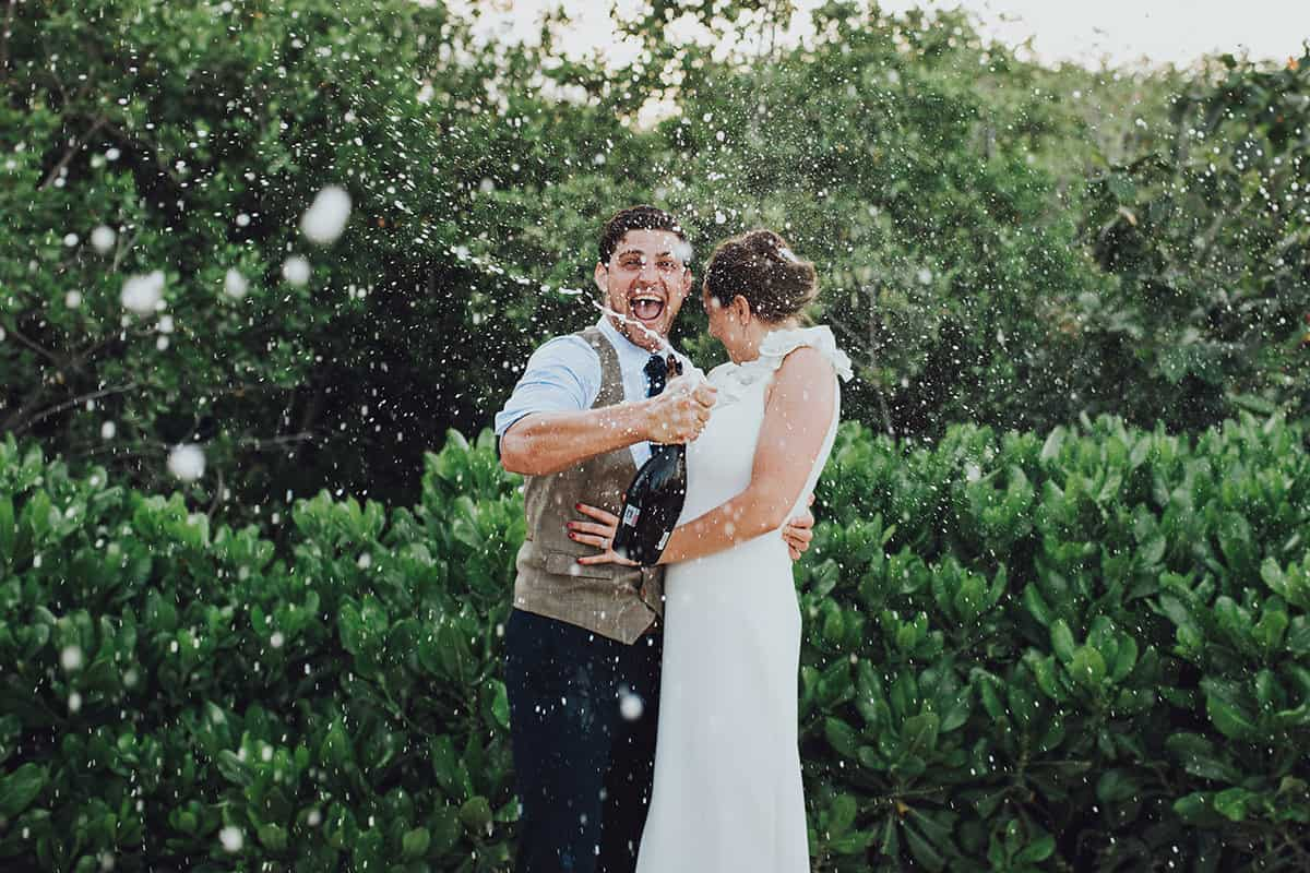 Groom sprays champagne bottle over bride and groom whilst laughing
