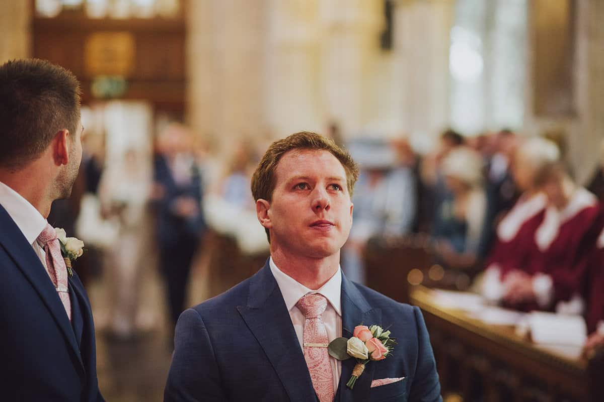 Groom waits nervously for his bride in a church on their wedding day