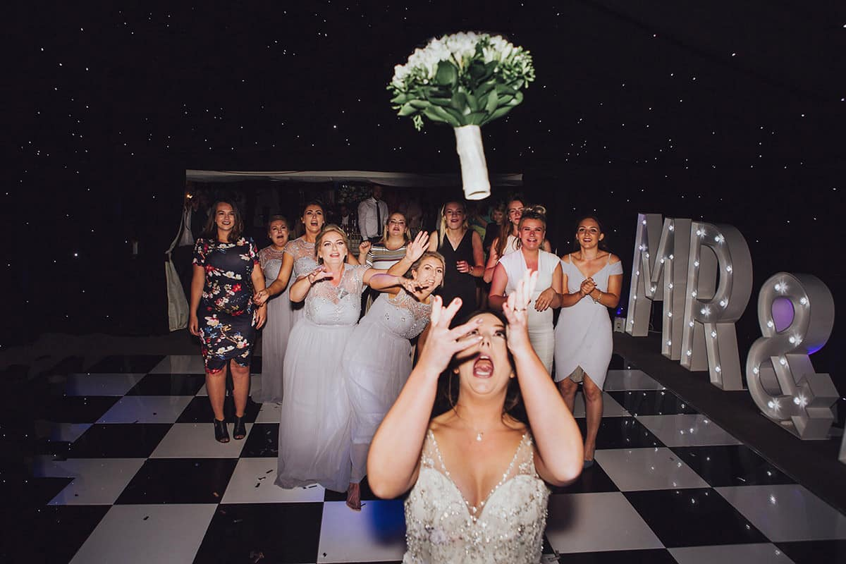 bride throwing bouquet to girls on wedding dancefloor