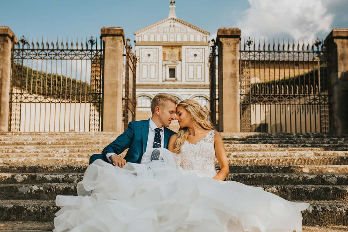 bride and groom sitting outside italian church