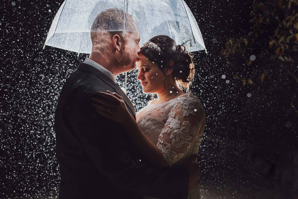 Bride and Groom stand under an umbrella at night whilst it pours with rain