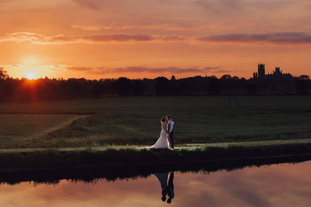 Bride and Groom stand by a lake at sunset at The Old Hall in Ely
