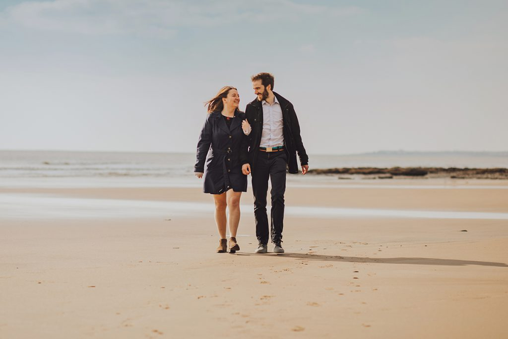An engaged couple enjoying a welsh beach at sunset