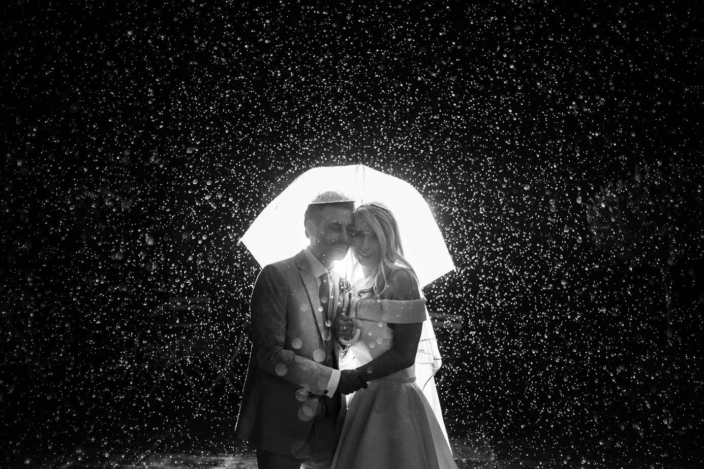 married couple standing under umbrella in the rain at night